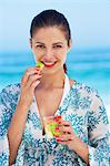 Beautiful brunette eating fruit on beach Stock Photo - Premium Rights-Managed, Artist: urbanlip.com, Code: 847-06727287