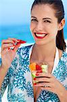 Beautiful brunette eating fruit on beach Stock Photo - Premium Rights-Managed, Artist: urbanlip.com, Code: 847-06727290