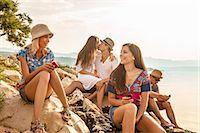 Croatia, Dalmatia, Young people at the seaside, using phones Stock Photo - Premium Royalty-Freenull, Code: 6115-06733080