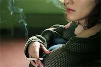 Portrait of the girl with a cigarette on a green background Stock Photo - Royalty-Freenull, Code: 400-06737296