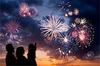 The happy family looks beautiful colorful holiday fireworks in the evening sky with majestic clouds,  long exposure Stock Photo - Royalty-Freenull, Code: 400-06744743