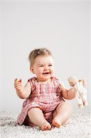 Portrait of Baby Girl Laughing and holding Teddy Bear, Studio Shot Stock Photo - Premium Royalty-Freenull, Code: 600-06752370