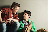 Teenagers looking at Cell Phone, Studio Shot Stock Photo - Premium Royalty-Freenull, Code: 600-06752465