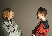 Teenage Boy and Girl looking at Each Other and Laughing, Studio Shot Stock Photo - Premium Royalty-Freenull, Code: 600-06752489