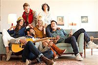 Group of well styled young adults playing guitar and singing on a couch. Stock Photo - Premium Rights-Managednull, Code: 700-06752634