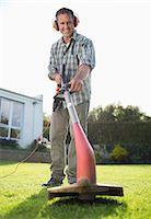 Man using weed whacker in backyard Stock Photo - Premium Royalty-Freenull, Code: 6113-06753258