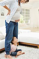 Girl holding pregnant mother's legs Stock Photo - Premium Royalty-Freenull, Code: 6113-06753623