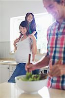 portrait of pregnant woman - Pregnant mother and daughter watching father toss salad Stock Photo - Premium Royalty-Freenull, Code: 6113-06753637