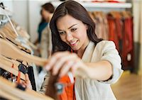 Woman shopping in clothes store Stock Photo - Premium Royalty-Freenull, Code: 6113-06753727