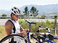 Man adjusting bicycle outdoors Stock Photo - Premium Royalty-Freenull, Code: 6113-06754077