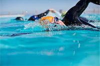 swimming pool water - Triathletes in wetsuit splashing in pool Stock Photo - Premium Royalty-Freenull, Code: 6113-06754098