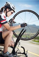 Cyclist adjusting tire on rural road Stock Photo - Premium Royalty-Freenull, Code: 6113-06754158