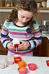 Girl decorating cupcakes in kitchen Stock Photo - Premium Royalty-Free, Artist: Cultura RM, Code: 6113-06754185