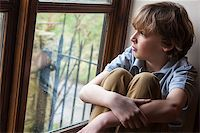 sad child sitting - Sad young boy sitting, thinking and looking out of rain covered window Stock Photo - Royalty-Freenull, Code: 400-06772407