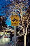 Pedestrian crosses at sign near shoppping mall, sign reads: Caution Shoppers Crossing, Austin, Texas, USA