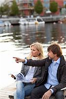 people sitting on bench - Couple sitting by water Stock Photo - Premium Royalty-Freenull, Code: 6102-06777357
