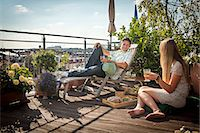 Couple Relaxing On Roof Terrace, Munich, Bavaria, Germany, Europe Stock Photo - Premium Royalty-Freenull, Code: 6115-06778656