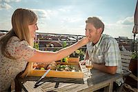 Woman Feeding Man On Balcony, Munich, Bavaria, Germany, Europe Stock Photo - Premium Royalty-Freenull, Code: 6115-06778663