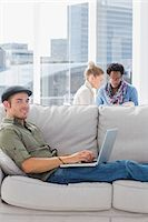 Cheerful worker using his laptop while laying on a couch Stock Photo - Premium Royalty-Freenull, Code: 6109-06781503