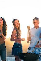 Smiling friends cooking barbecue on the beach Stock Photo - Premium Royalty-Freenull, Code: 6109-06781769