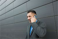 Close-up portrait of businessman standing in front of wall of building using cell phone, Mannheim, Germany Stock Photo - Premium Royalty-Freenull, Code: 600-06782190