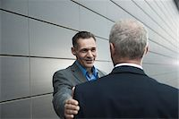 Mature businessmen standing in front of wall, talking Stock Photo - Premium Royalty-Freenull, Code: 600-06782198