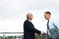 Mature businessmen standing by railing, shaking hands outdoors, Mannheim, Germany Stock Photo - Premium Royalty-Freenull, Code: 600-06782202