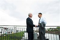 Mature businessmen standing by railing, shaking hands outdoors, Mannheim, Germany Stock Photo - Premium Royalty-Freenull, Code: 600-06782203