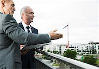 Mature businessmen standing on outdoor balcony, talking and overlooking city, Mannheim, Germany Stock Photo - Premium Royalty-Freenull, Code: 600-06782207
