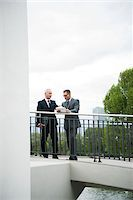 Mature businessmen standing on outdoor bridge talking, Mannheim, Germany Stock Photo - Premium Royalty-Freenull, Code: 600-06782214