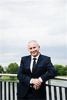 Portrait of mature businessman standing on bridge, smiling at camera and leaning on railing, Mannheim, Germany Stock Photo - Premium Royalty-Freenull, Code: 600-06782224