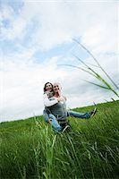 Mature couple in field of grass, man giving piggyback ride to woman, Germany Stock Photo - Premium Royalty-Freenull, Code: 600-06782246