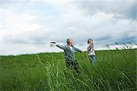 Mature couple running in field of grass, Germany Stock Photo - Premium Royalty-Freenull, Code: 600-06782248