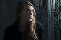 Portrait of young woman behind window, wet with raindrops, looking up Stock Photo - Premium Royalty-Freenull, Code: 600-06786759