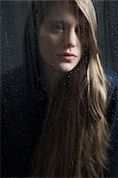 Portrait of young woman behind window, wet with raindrops, wearing hoodie Stock Photo - Premium Royalty-Freenull, Code: 600-06786761