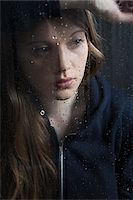 Portrait of young woman behind window, wet with raindrops, wearing hoodie Stock Photo - Premium Royalty-Freenull, Code: 600-06786764