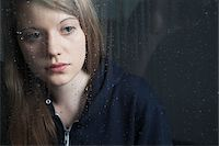 Portrait of young woman behind window, wet with raindrops, wearing hoodie Stock Photo - Premium Royalty-Freenull, Code: 600-06786765
