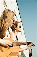 Young women sitting outdoors, hanging out and playing guitar, Mannheim, Germany Stock Photo - Premium Royalty-Freenull, Code: 600-06786781