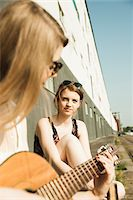 Young women sitting outdoors, hanging out and playing guitar, Mannheim, Germany Stock Photo - Premium Royalty-Freenull, Code: 600-06786782