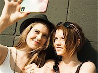 Close-up of young women taking photo of themselves with smart phone Stock Photo - Premium Royalty-Freenull, Code: 600-06786784