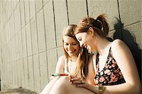 Young women sitting and leaning against wall, looking at smart phone together Stock Photo - Premium Royalty-Freenull, Code: 600-06786788