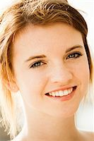 Close-up portrait of teenage girl outdoors, smiling at camera Stock Photo - Premium Royalty-Freenull, Code: 600-06786804