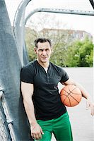 Portrait of mature man standing on outdoor basketball court, Germany Stock Photo - Premium Royalty-Freenull, Code: 600-06786825