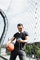 Mature man standing on outdoor basketball court holding basketball and looking at MP3 player, Germany Stock Photo - Premium Royalty-Freenull, Code: 600-06786837