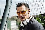 Close-up portrait of mature man wearing sunglasses with headphones around neck, Germany