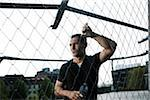 Mature man leaning against chain-link fence on outdoor basketball court, holding bottle of water, Germany