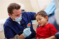 Boy patient receiving complimentary lollipop after a dental checkup by male dentist. Stock Photo - Premium Rights-Managednull, Code: 700-06786928