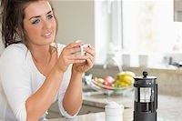 Woman thinking over coffee at breakfast in kitchen Stock Photo - Royalty-Freenull, Code: 400-06800448