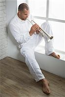 Portrait of Musician Playing Trumpet by Window, Italy Stock Photo - Premium Royalty-Freenull, Code: 600-06803960