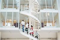 Business people climbing spiral staircase in office Stock Photo - Premium Royalty-Freenull, Code: 698-06804003